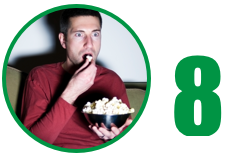 Image: Person on a couch eating popcorn