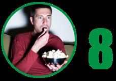 Imagem: pessoa sentada no sofá e comendo pipoca