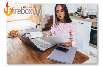 Woman working at a dining room table with papers and a laptop with a FireboxV logo in the left side