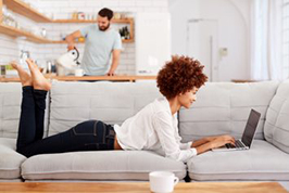 Woman laying on a couch working on her laptop