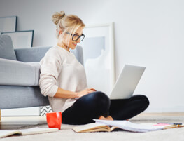 Thumbnail: Woman sitting in front of her couch cross-legged, working on a laptop