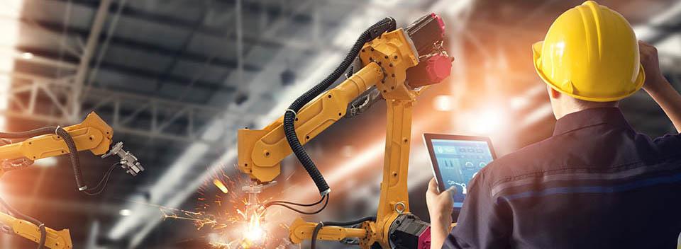 Arbeiter mit gelbem Schutzhelm bei der Bedienung einer Maschine mit einem Tablet-Computer