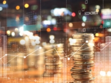 Pile of coins in front of a line graph and blurry cityscape