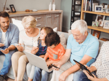 A large family sitting together on a couch on different mobile devices