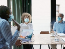 Masked workers sitting around a conference room table