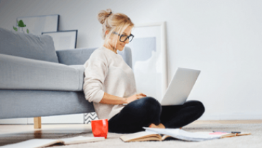 Woman sitting in front of her couch working on a laptop