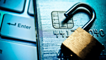 Open padlock sitting on top of a credit card and a keyboard