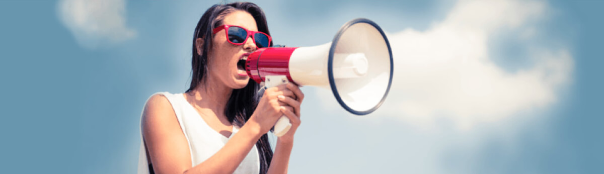 Woman shouting into a megaphone against a backdrop of blue sky
