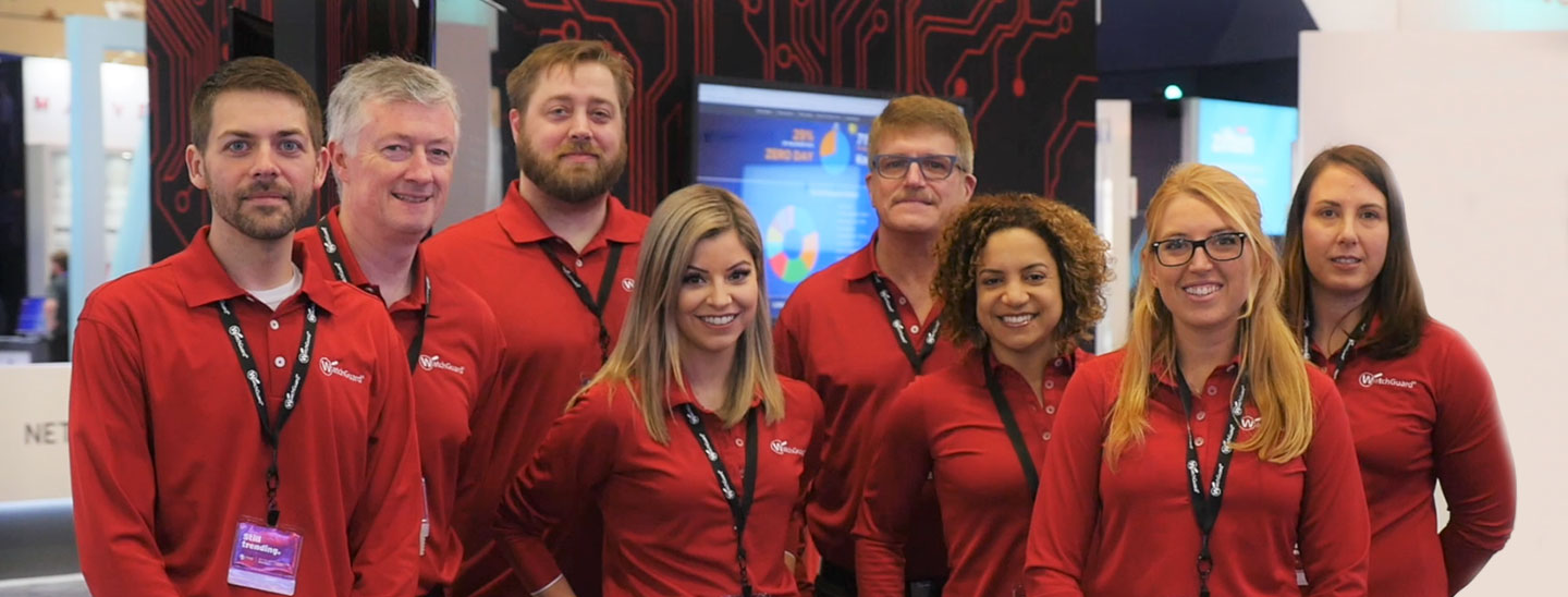 WatchGuard Employees in red shirts in front of a trade show booth